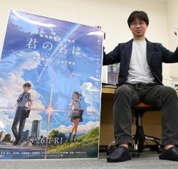 画像:映画「君の名は。」のポスターを手にする新海誠監督