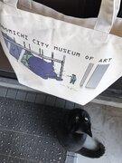 尾道市立美術館の「猫と警備員の攻防」がトートバッグに 美術館に入りたい黒猫が巨大な化け猫に変化